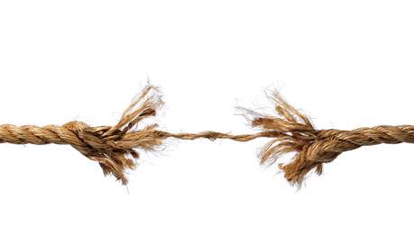 Frayed rope about to break isolated over a white background